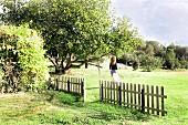 Sommerliche grüne Landschaft mit Lattenzaun und einer Frau, die den geschützteren Bereich verlässt