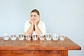 Verzweifelte Frau mit mehreren Wassergläsern