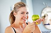 Lachende Frau misst den Umfang eines Apfels