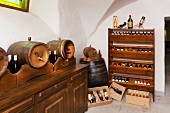 Weinregal, Weinkisten und Fässer in einem Weinkeller