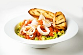 Cold Calamari Salad Over Spinach Noodles with Grilled Bread Slices