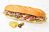 Large Submarine Sandwich with Pickles and Olives; White Background