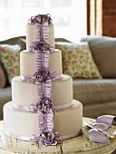 Vierstöckige Hochzeitstorte mit fliederfarbenen Satinbändern, -blumen und -schleifen dekoriert