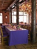 Festliche Tafel mit lila Tischdecke und einer farblich abgestimmten Tischdekoration