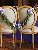 Chairs Decorated with Fresh Garland and Ribbon for the Bride and Groom at a Wedding Reception