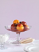 Poached stone fruits in a glass bowl
