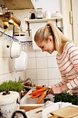 Woman washing carrots in sink