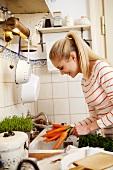Junge Frau wäscht Möhren in der Küche