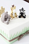 A white cake decorated with animals made from fondant icing