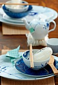 An Asian place setting - chopsticks and rice noodles in a bowl in front of a small teapot