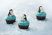 Three cupcakes decorated with penguins