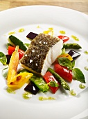 Fried cod fillet with spring vegetables, basil and lime oil