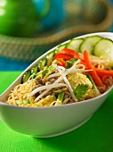 Oriental noodle dish with chicken, vegetables and coconut sauce