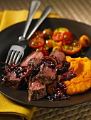 Steak with a red wine-mushroom sauce, pumpkin puree and cocktail tomatoes