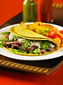 A taco filled with beef, blue cheese and rocket