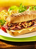 Toasted steak sandwich with onion rings and cheese
