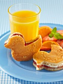 Duck-shaped pancakes filled with strawberry jam with a glass of orange and fresh fruit