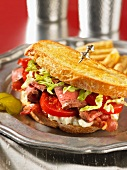 A steak sandwich with tomatoes and bacon