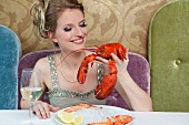 Woman holding lobster in restaurant