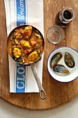 Pan of Provençal fish soup with mussels and a dish for the mussel shells