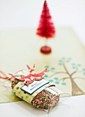 Parcel of Christmas biscuits with hundreds-and-thousands and red tree ornament in background