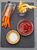 White and Sweet Potato French Fries in Glass Containers with Ketchup and Salt