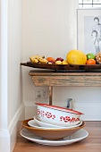 Various bowls and dishes in front of full fruit bowl on old wooden bench