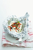 Grilled cheep's cheese with chilli and oregano in tin foil
