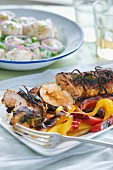 Roast pork roulade with harissa and a pepper medley with potato salad
