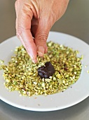 A truffle praline being rolled in pistachios