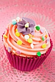 A cupcake decorated with buttercream, sugar sprinkles and a sugar flower