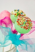 Cake pops decorated with colourful sugar sprinkles and bows