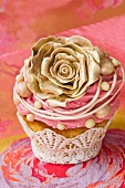 A cupcake decorated with a gold rose and buttercream