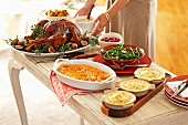 Woman Setting Holiday Table with Roast Turkey, Squash and Mashed Potato Casseroles