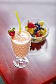 A Pineapple, Strawberry, Blueberry Smoothie in a Glass with a Straw; Bowl of Fruit