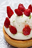 Tartlet topped with lime cream and wild strawberries