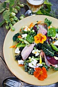 Colourful autumnal salad with cress flowers and dried lamb