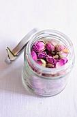 Dried rose petals in a screw top jar