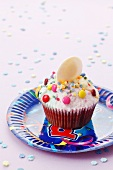 A cupcake decorated with colourful sugar sprinkles and chocolate beans