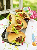 Pita breads filled with meat patties, salad, sweetcorn, cucumber and tomato