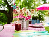 Sweet sandwich 'lollipops' and a glass of apple punch on a table outdoors
