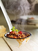 Steaming chilli con carne in a ladle