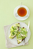 Wholemeal bread topped with chicken breast, lettuce and cucumber with a cup of tea