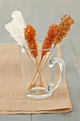 Brown and white rock sugar sticks in a glass jug