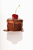 Individual Chocolate Dessert with Chocolate Sauce and a Cherry; White Background