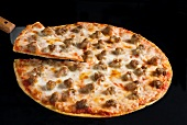 Thin Crust Sausage Pizza on a Black Background with a Slice on a Spatula