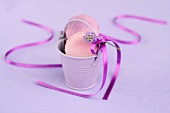 Macaroons with a ribbon and lavender flowers in a mini bucket