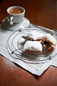 Chocolate Filled Beignets on a Wire Rack Dusted with Powdered Sugar