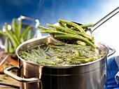Grüne Bohnen in Topf mit kochendem Wasser geben