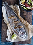 Trout with mustard and orange zest on baking paper